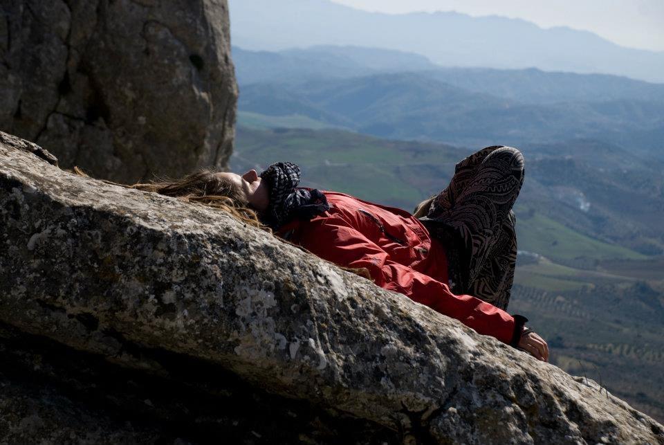 Девушка лежит на скале смотрит на солнце