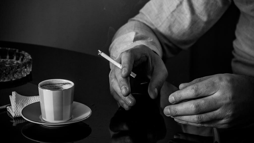 Руки Ашота с сигаретой, чашка с армянским кофе на столе