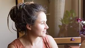 Девушка смотрит в окно и улыбается