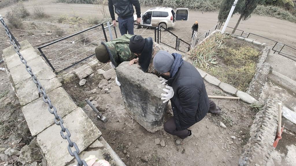 Трое мужчин пытаются сдвинуть хачкар