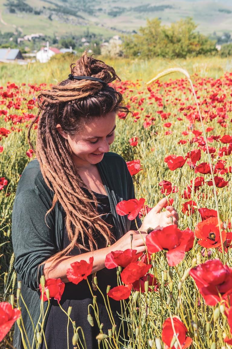 девушка стоит в поле маков улыбается